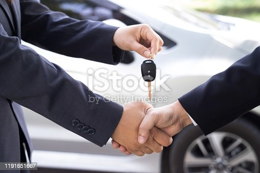 939005154 istock photo Businessmen have agreed to buy - sell new cars at the motor show. With a special privilege promotion 1191651667