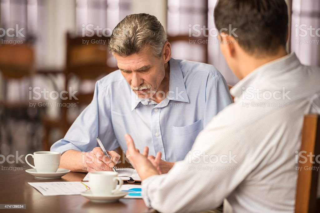 Businessmen having a meeting in a cafe stock photo