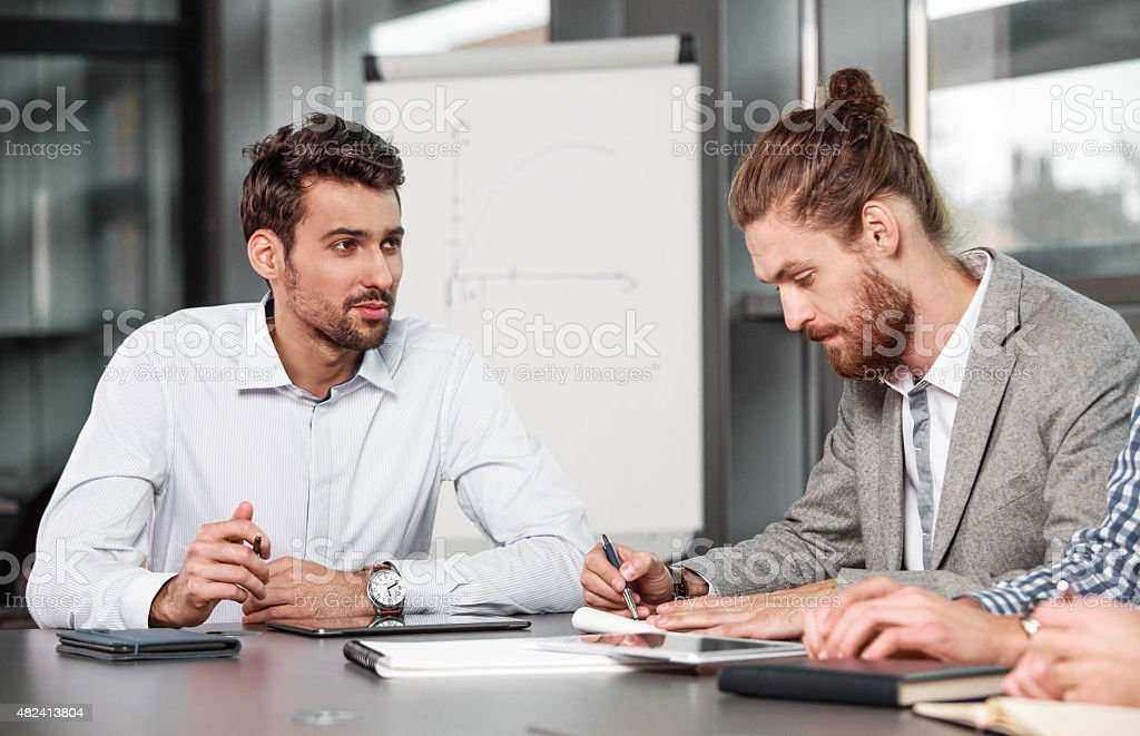 Businessmen having meeting in a board room Businessmen discussing in a board room at the conference table in an office together. Flipchart in the background. 2015 Stock Photo