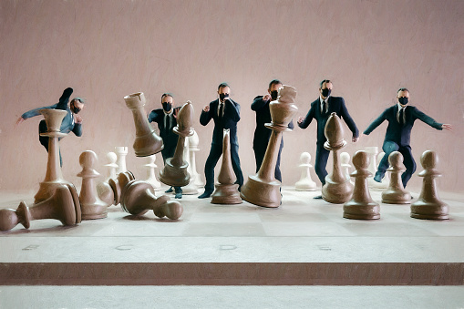 Businessmen hitting chess figures, 3D generated image.