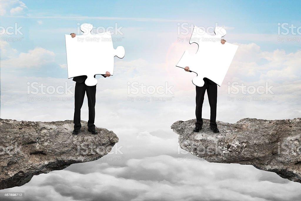Geschäftsleute holding jigsaw puzzle, um sich auf Klippe mit clou – Foto
