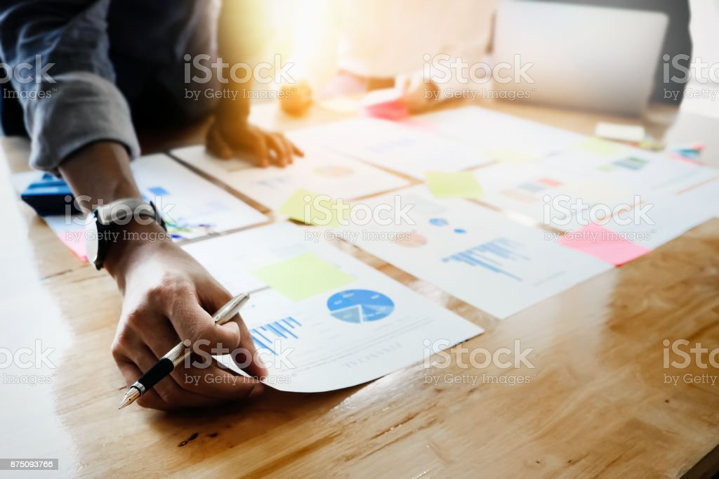 Businessmen holding pens and holding graph paper are meeting to plan sales to meet targets set in next year. stock photo
