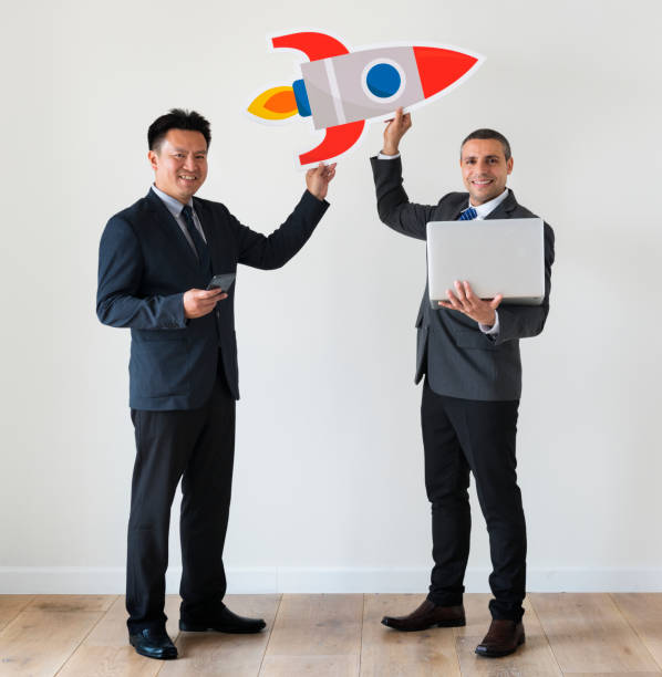 businessmen holding rocket icon - rocket logo stock photos and pictures