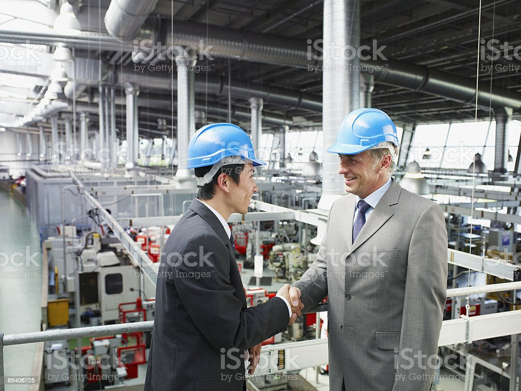 Businessmen in hard-hats shaking hands royalty-free stock photo