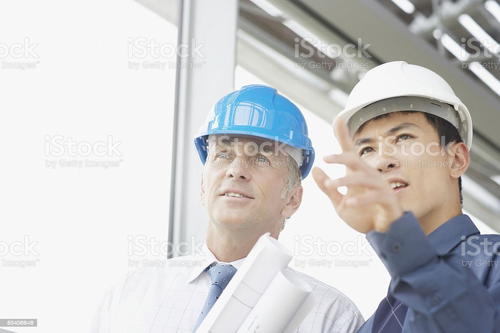 Businessmen in hard-hats talking royalty-free stock photo