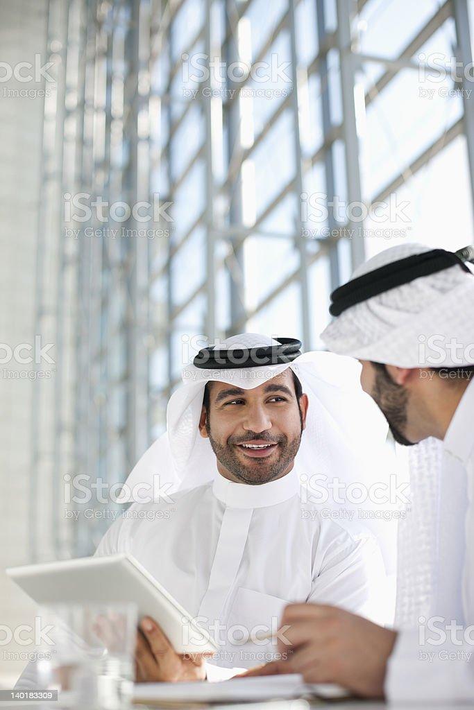 Businessmen in kaffiyehs using digital tablet stock photo
