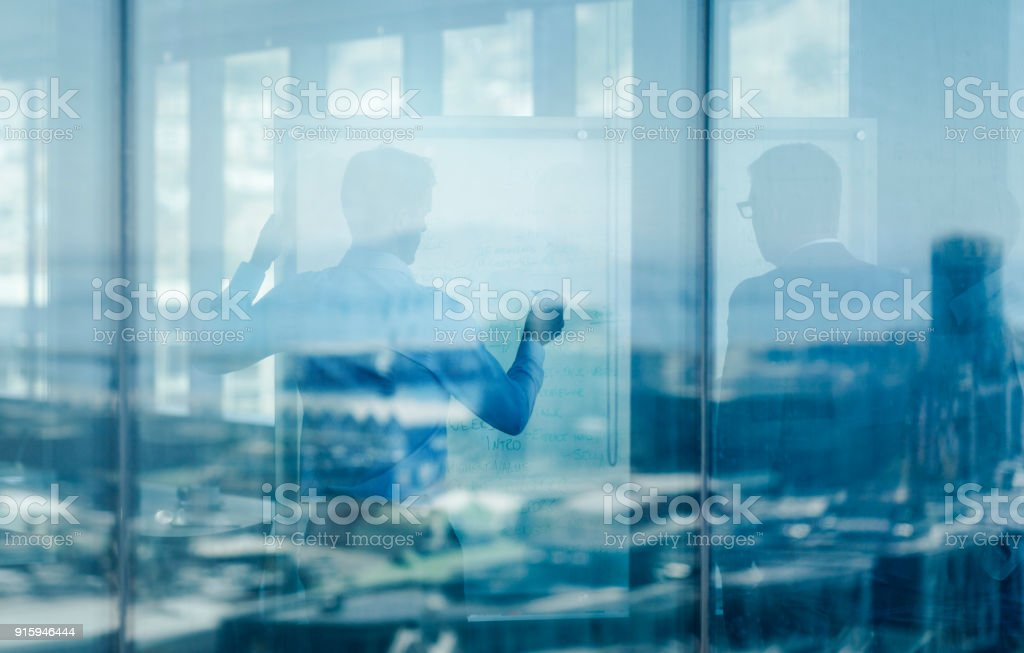 Businessmen in meeting seen through glass window stock photo