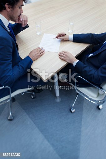 istock Businessmen in negotiation at meeting table 637912230