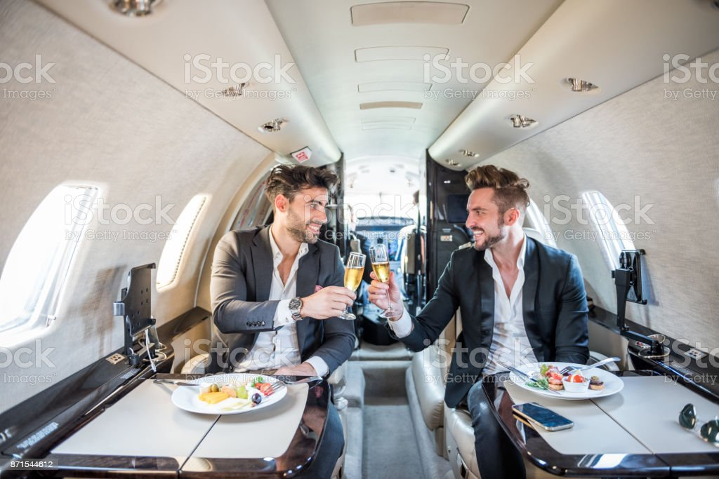 Businessmen in private jet airplane stock photo