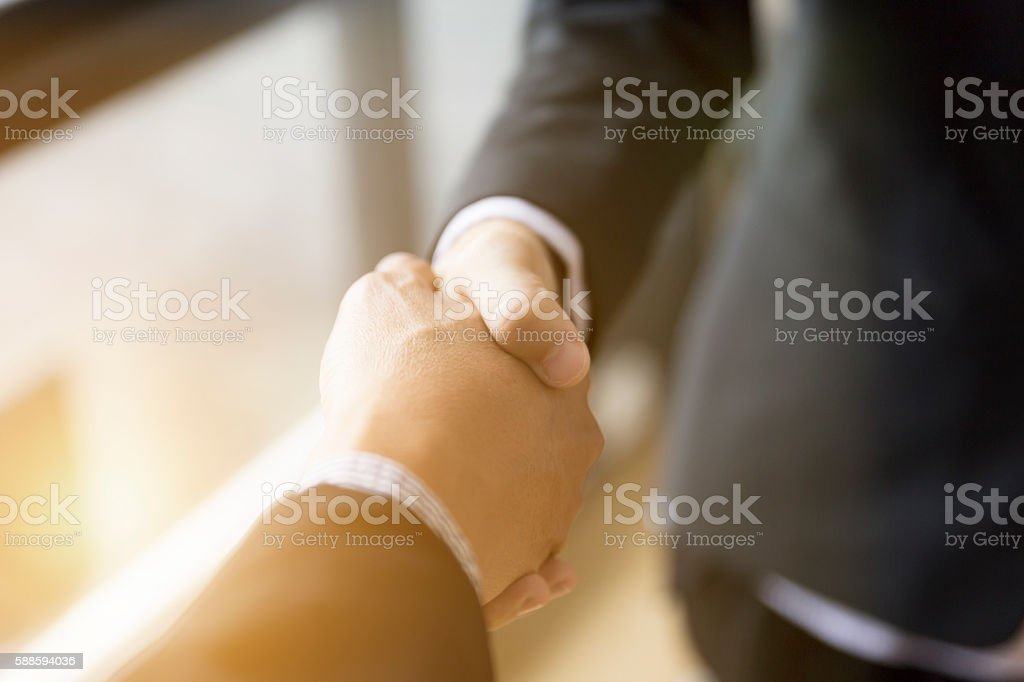 businessmen in suit shaking hands beside window - stock photo