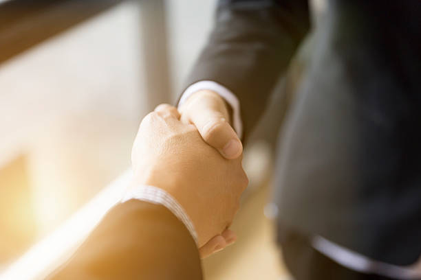businessmen in suit shaking hands beside window - – Foto