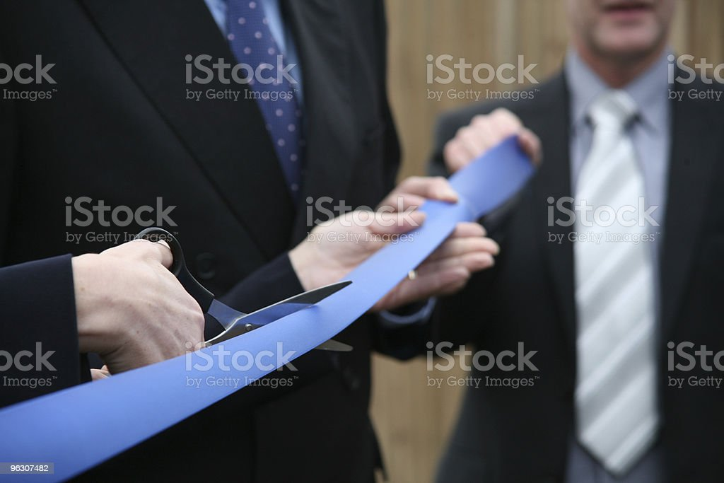 Businessmen in suits holding scissors cutting a blue ribbon stock photo