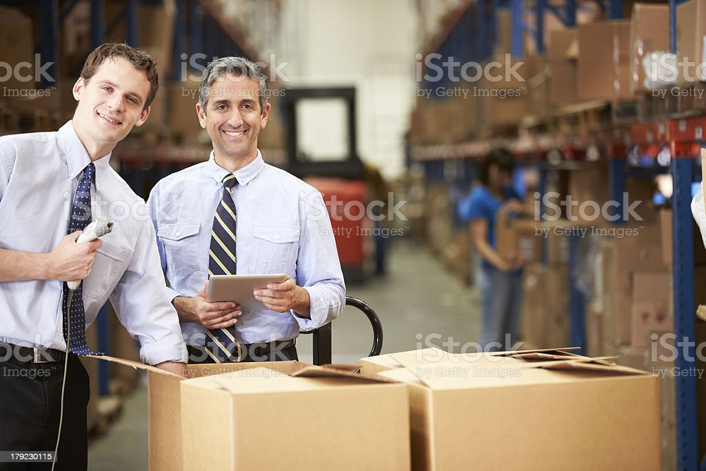 Businessmen inspecting merchandise in warehouse royalty-free stock photo