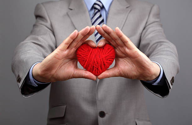 businessmen is holding out a red heart - passion stock pictures, royalty-free photos & images