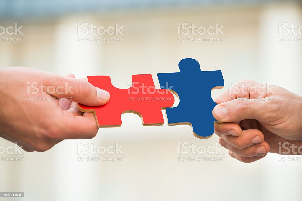 Businessmen Joining Jigsaw Pieces stock photo