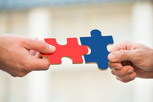 businessmen joining jigsaw pieces - puzzleteile stock-fotos und bilder