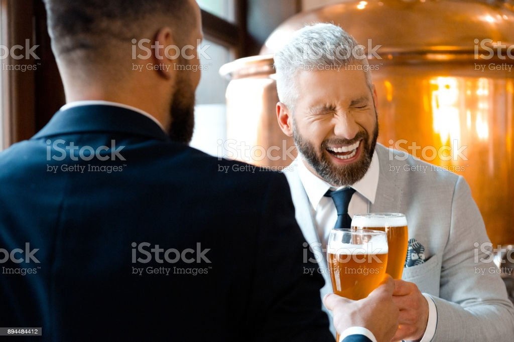 Businessmen laughing and toasting beers in microbrewery Two businessmen having beers in the microbrewery and laughing. Mature businessman laughing while toasting beer with colleague in brewery. Adult Stock Photo