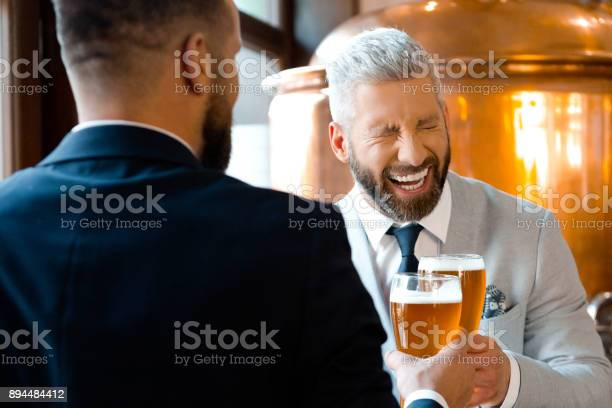 Businessmen Laughing And Toasting Beers In Microbrewery Stock Photo - Download Image Now