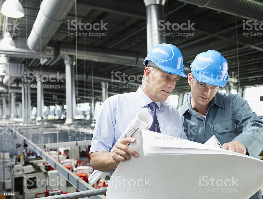 Businessmen looking at blueprints in factory stock photo