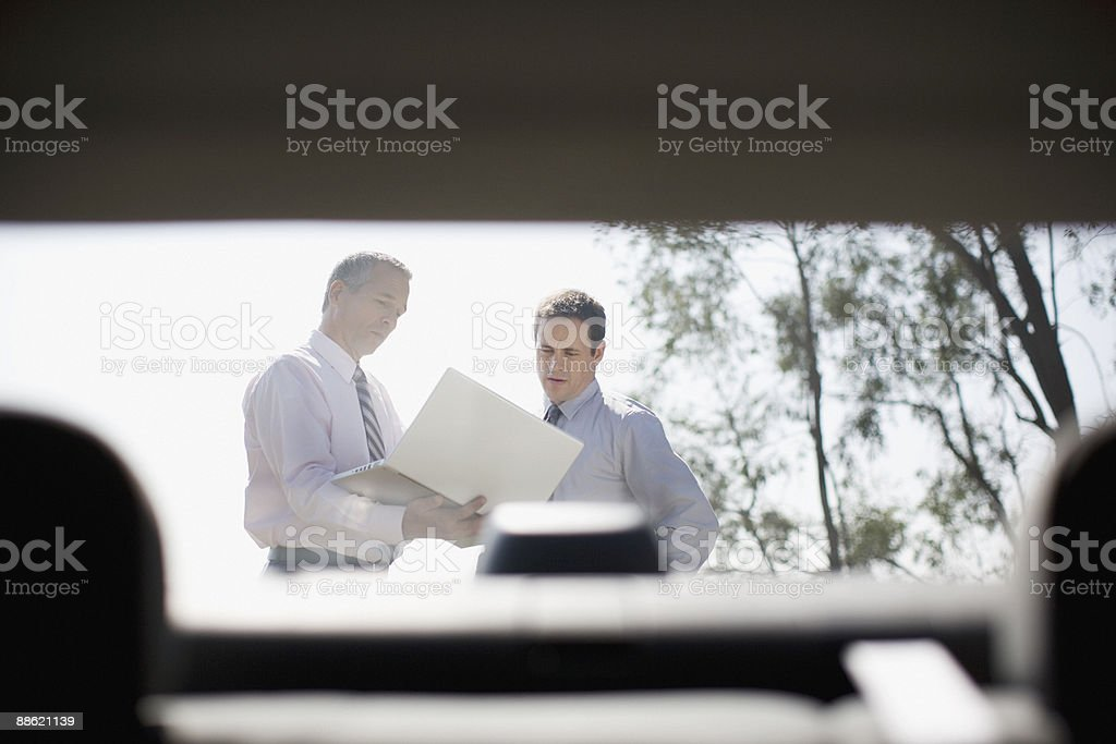 Businessmen looking at laptop outdoors 免版稅 stock photo