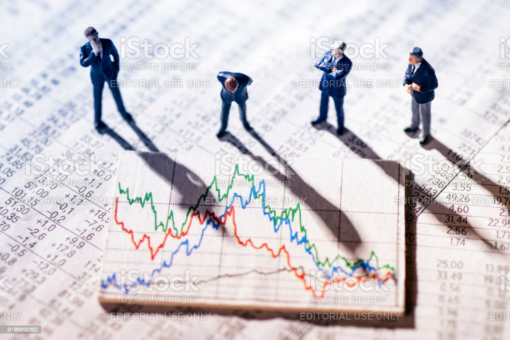 Businessmen looking at market charts Frankfurt, Hesse, Germany - January 11, 2018: Figures of businessmen are skeptical looking at stock market charts. Analyzing Stock Photo