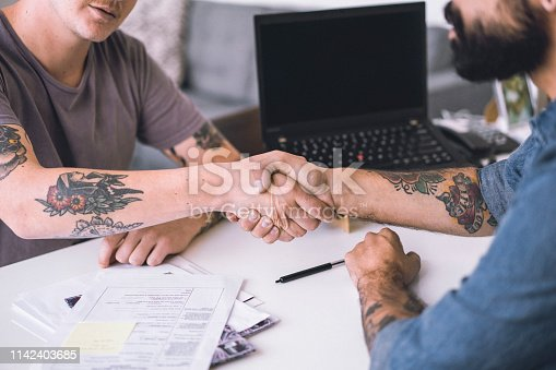 Cropped image of businessmen shaking hands over documents. Male professionals are making a business deal at table. They are in creative office. Businessman Shaking Hands At Interview.