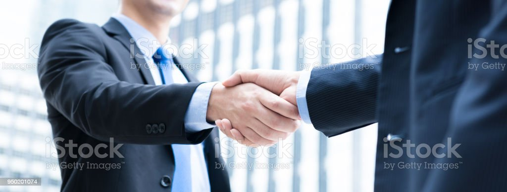 Businessmen making handshake Businessmen making handshake the city - business etiquette, congratulation, merger and acquisition concepts, panoramic banner Adult Stock Photo
