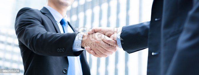 Businessmen making handshake the city - business etiquette, congratulation, merger and acquisition concepts, panoramic banner