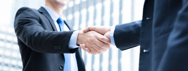 Businessmen making handshake Businessmen making handshake the city - business etiquette, congratulation, merger and acquisition concepts, panoramic banner alliance stock pictures, royalty-free photos & images