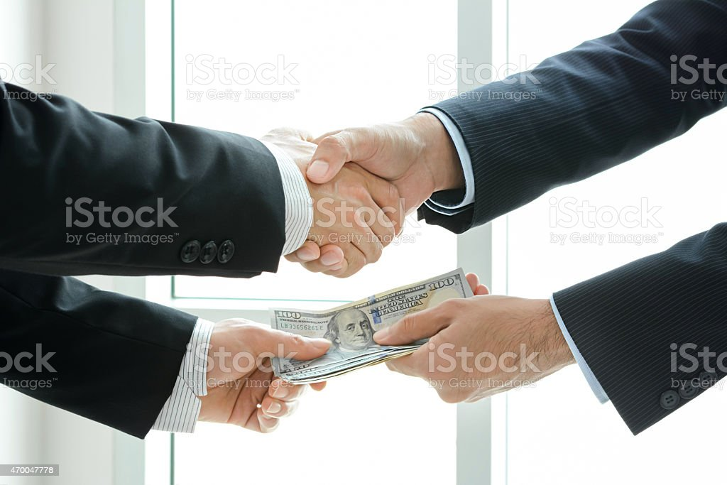 Businessmen making handshake while passing money stock photo
