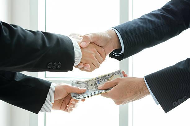 empresário fazendo aperto de mão enquanto passando dinheiro - corruption imagens e fotografias de stock