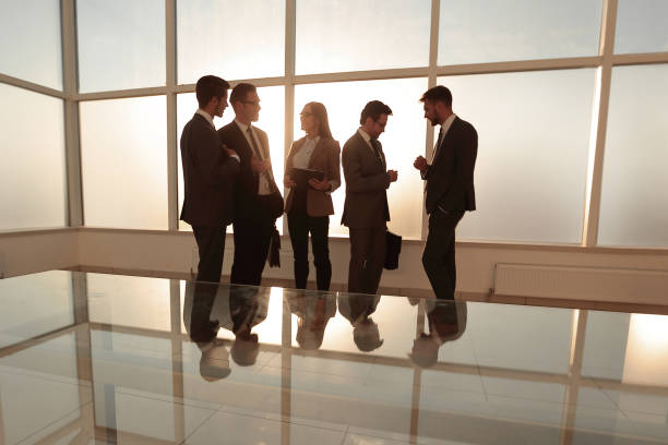Businessmen near a window in a meeting room stock photo