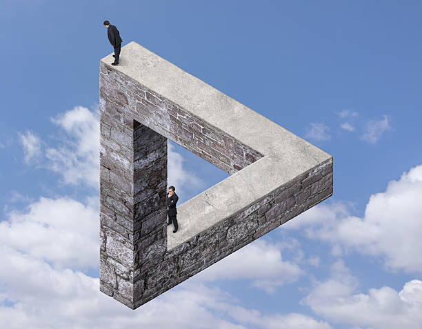 businessmen on the impossible triangle made with stone - illusion stock photos and pictures