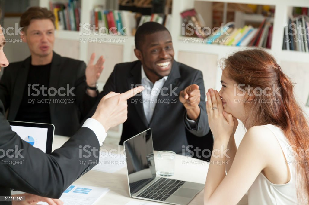 Businessmen pointing fingers congratulating businesswoman with achievement at office meeting stock photo