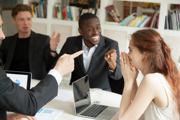 businessmen pointing fingers congratulating businesswoman with achievement at office meeting - ammirazione foto e immagini stock