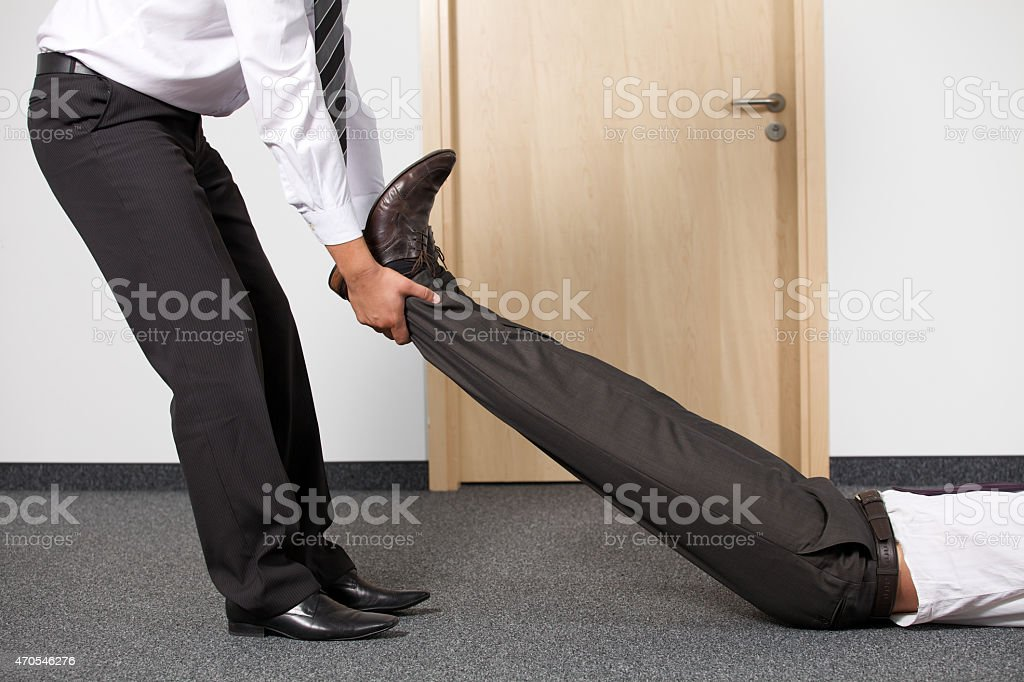 Businessmen pulling colleague's leg at office royalty-free stock photo