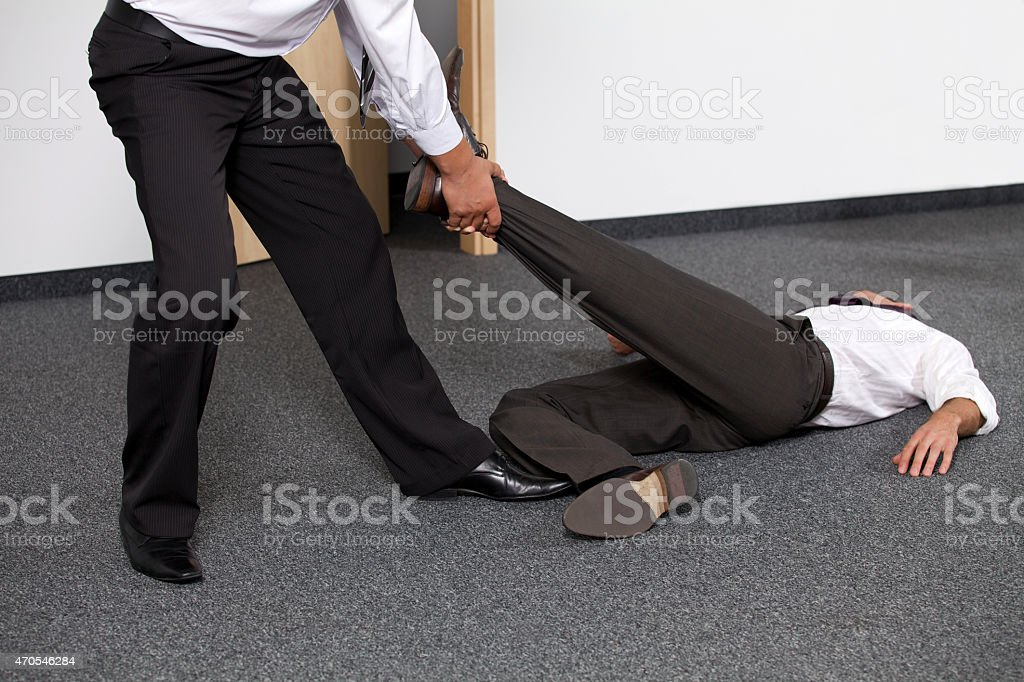 Businessmen pulling colleague's leg at office stock photo