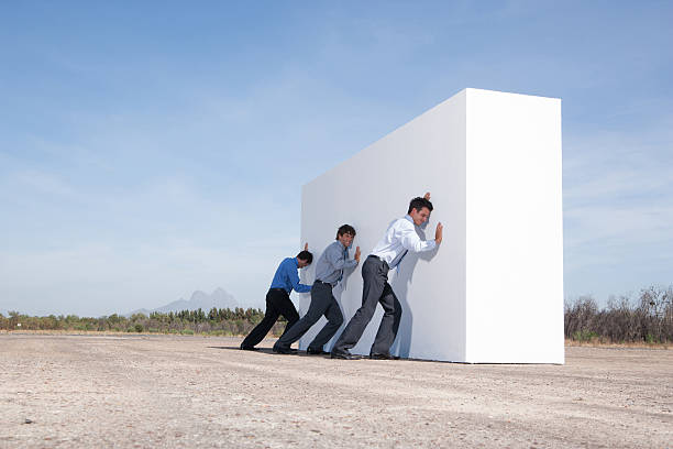 Businessmen pushing wall outdoors stock photo