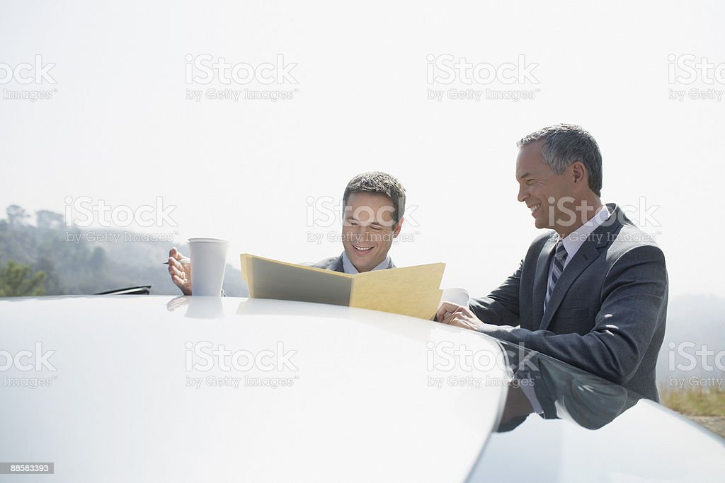 Businessmen reviewing paperwork outdoors royalty-free stock photo
