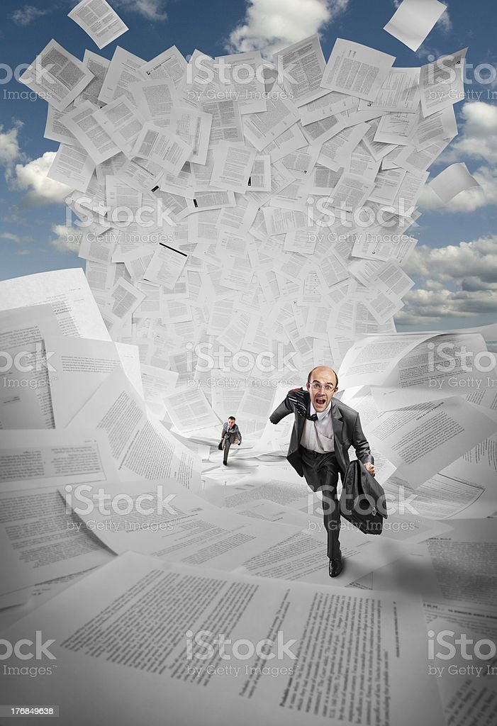 Businessmen running away from wave of documents stock photo