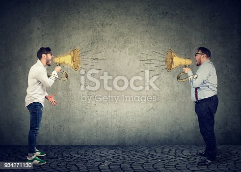 istock Businessmen screaming into a megaphone at each other 934271130