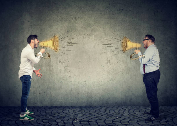 Businessmen screaming into a megaphone at each other Businessmen screaming into a megaphone at each other having an angry debate confrontation stock pictures, royalty-free photos & images