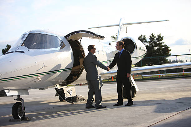 Businessmen shake hands by corporate jet stock photo