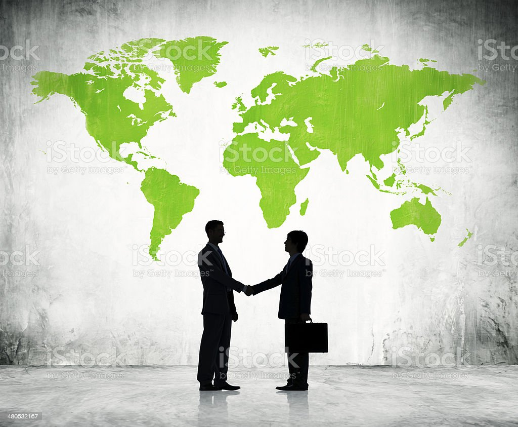 Businessmen shake hands with green land background stock photo