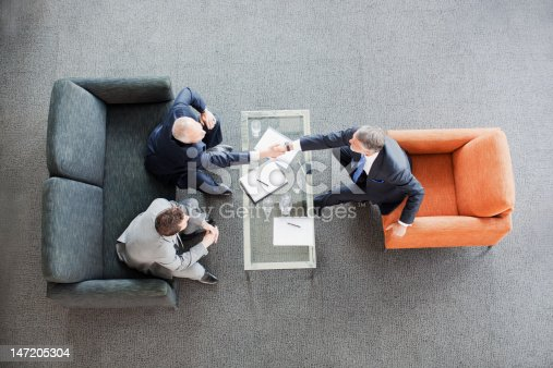 istock Businessmen shaking hands across coffee table in office lobby 147205304