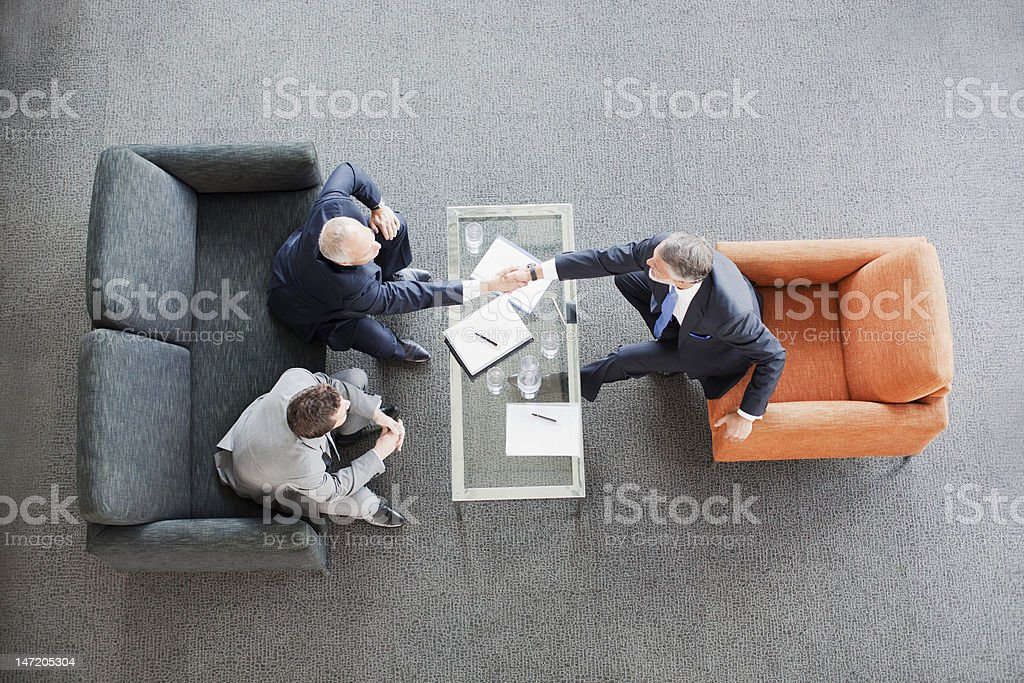 Businessmen shaking hands across coffee table in office lobby stock photo