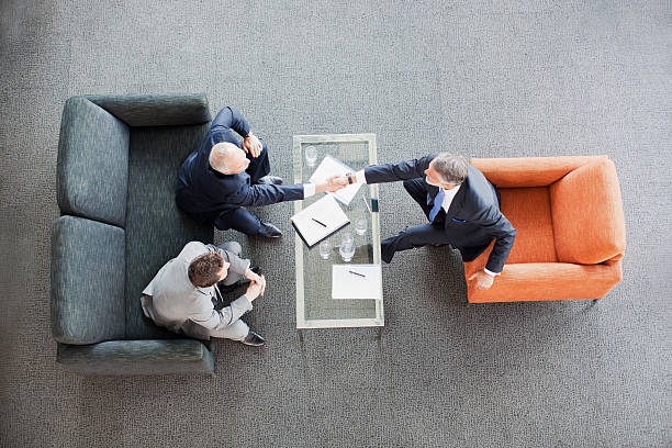 businessmen shaking hands across coffee table in office lobby - satmak stok fotoğraflar ve resimler