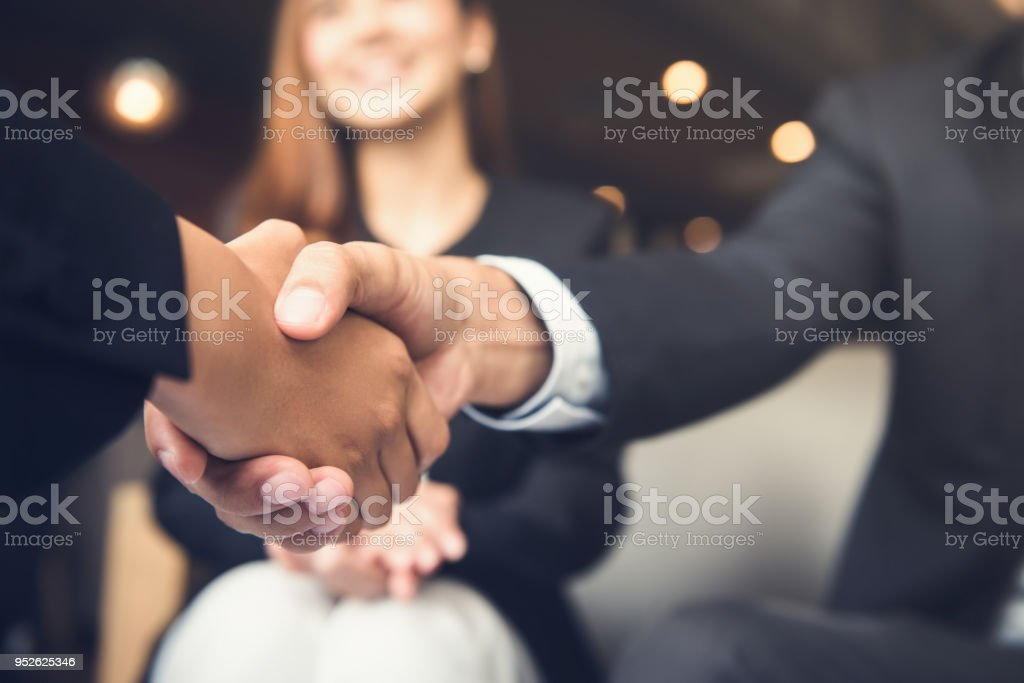 Businessmen shaking hands after meeting in a cafe stock photo