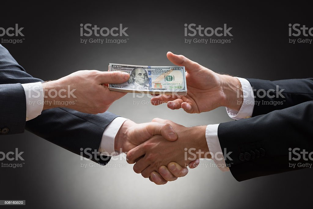 Businessmen Shaking Hands And Receiving Money stock photo