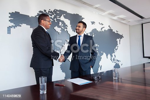 Pair of men team of well dressed suit and tie businessmen executive people in a row at wood conference meeting table talking shaking hands handshake agreement solution positive emotion partnership discussing negotiation planning strategy plans with world map globe earth on wall modern contemporary mural with contracts documents paperwork pens on table prepared decisions choices challenge the way forward future opportunity merger and acquisition combined strength aspirations fine print multi-ethnic Middle Eastern Black